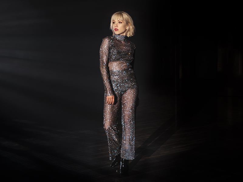 Carly Rae Jespen wearing a sheer, silvery bodysuit.