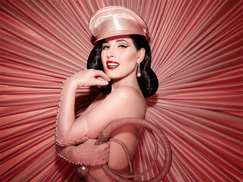 Dita Von Teese in front of a pink pleated wall.