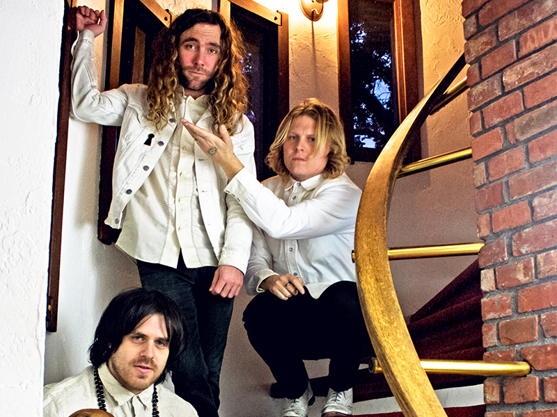 Three band members pose on a staircase