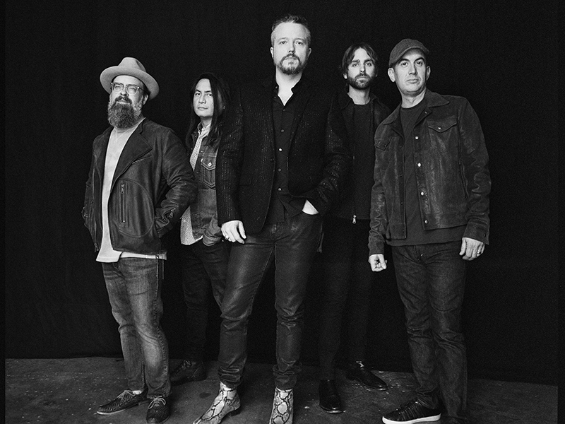 A black and white photo of Jason Isbell and The 400 Unit standing.