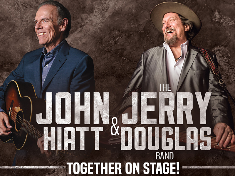 John Hiatt and Jerry Douglas holding guitars and laughing.