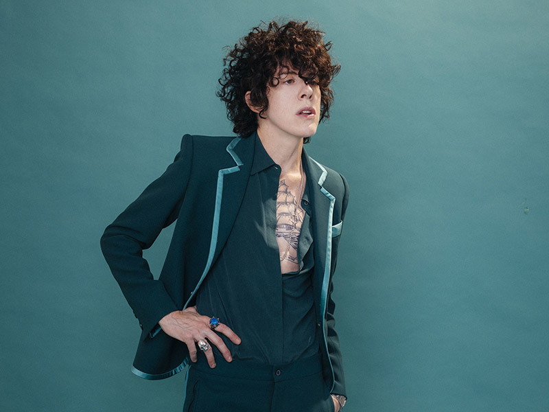LP wearing a suit with an open front shirt, leaning against an aqua wall.