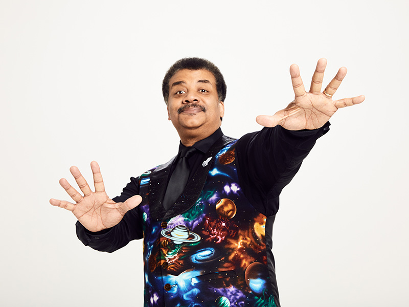 Neil deGrasse Tyson wearing a vest with planets on it.