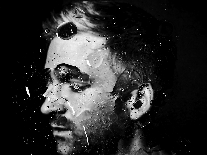 Ólafur Arnalds' face distorted by droplets of water.