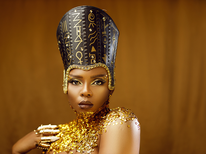 Yemi Alade adorned in gold and looking at the camera.